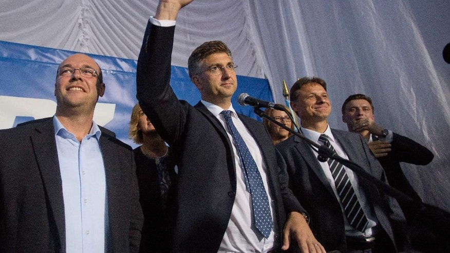 Andrej Plenkovic, center, leader of center-right HDZ party celebrates elections results at the party's headquarters in Zagreb, Croatia, early Monday, Sept. 12, 2016. Initial results of Croatia's early elections have shown that the conservatives were leading the vote, but won't be able to rule on their own, paving the way for another coalition government in the European Union's newest member state. (AP Photo/Darko Bandic)