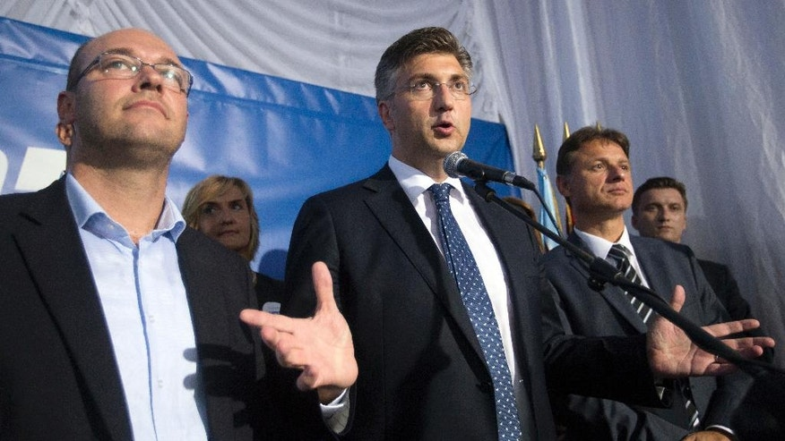 Andrej Plenkovic, center, leader of center-right HDZ party addresses the media and supporters at his party's headquarters in Zagreb, Croatia, early Monday, Sept. 12, 2016. Initial results of Croatia's early elections have shown that the conservatives were leading the vote, but won't be able to rule on their own, paving the way for another coalition government in the European Union's newest member state. (AP Photo/Darko Bandic)