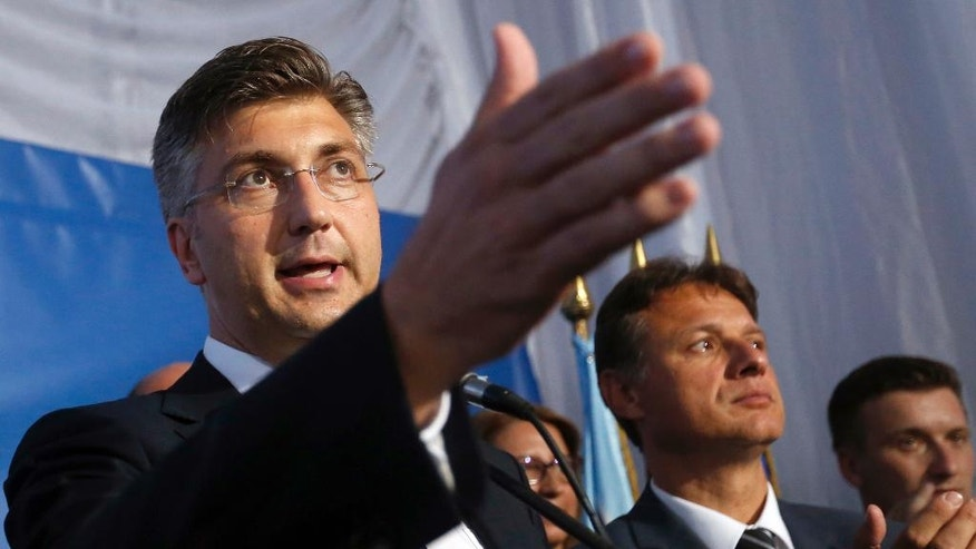 Andrej Plenkovic, left, leader of center-right HDZ party addresses the media and supporters at his party's headquarters in Zagreb, Croatia, early Monday, Sept. 12, 2016. Initial results of Croatia's early elections have shown that the conservatives were leading the vote, but won't be able to rule on their own, paving the way for another coalition government in the European Union's newest member state. (AP Photo/Darko Bandic)