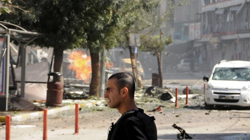 A security member stands after a car bomb attack in the city center of Van, eastern Turkey, Monday, Sept. 12, 2016. Turkey's state-run Anadolu news agency says an explosion near the ruling party headquarters and the governor's office in the eastern province of Van has left several wounded. The explosion occurred Monday morning on the first day of Eid al-Adha, an Islamic holiday.(DHA via AP)