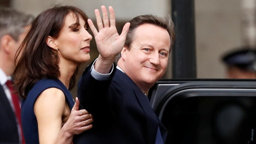 July 13, 2016: Britain's outgoing Prime Minister, David Cameron with his wife Samantha, waves in front of number 10 Downing Street, on his last day in office as Prime Minister, in central London, Britain.
