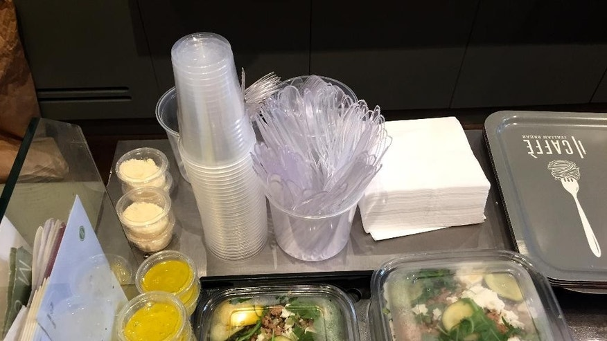 Plastic glasses, knives, forks and food boxes are pictured in a takeaway restaurant in Paris Tuesday, Sept. 6, 2016. France's efforts to reduce pollution will also affect nature lovers hitting the countryside for an outdoor meal. Under a controversial ban adopted last month, picnic-goers won't be able to drink their beloved rose wine in disposable plastic glasses, or to make ham and butter baguette sandwiches with plastic cutlery from 2020. (AP Photo/Bertrand Combaldieu)