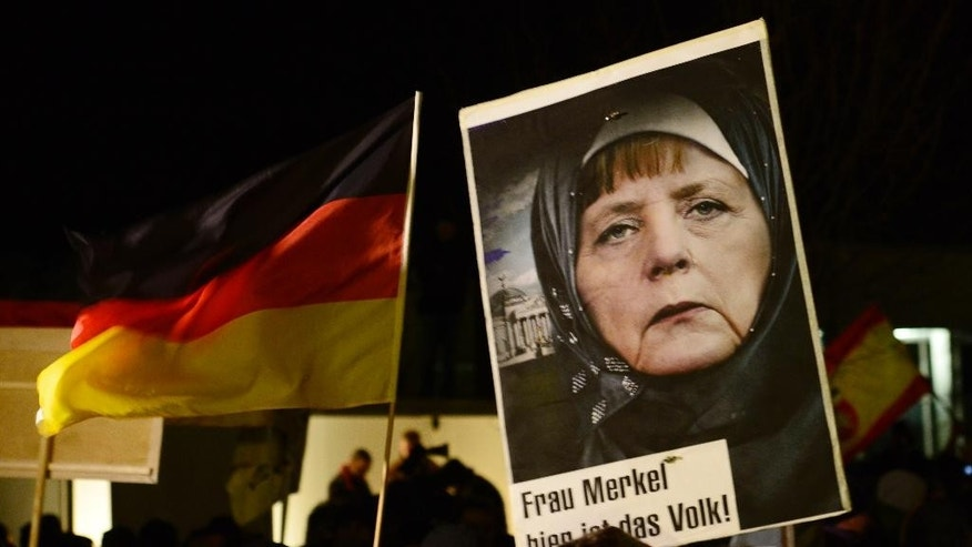 "FILE - In this Jan. 12, 2015 file picture a protestor holds a poster with an image of German Chancellor Angela Merkel wearing a headscarf in front of the Reichstag building with a crescent on top during a rally of the group Patriotic Europeans against the Islamization of the West, or PEGIDA, in Dresden, Germany.  Words on poster read : ""Mrs. Merkel, here is the people."" A leading member of the nationalist party Alternative for Germany is facing fierce criticism after calling for a racially charged term once favored by the Nazis to be rehabilitated. Party co-chairwoman Frauke Petry said in an interview published Sunday Sept. 11, 2016  that words such as ""voelkisch"" should be given ""a positive connotation."" Frequently used by the Nazis, the term refers to people who belong to a particular race.   (AP Photo/Jens Meyer,file)"