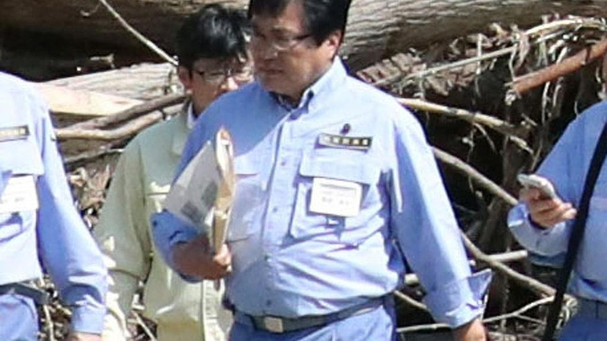 In this Sept. 1, 2016 photo,  Shunsuke Mutai,  Japan's vice minister of reconstruction, visits Iwaizumi, a northern Japanese town devastated by a deadly storm, northern Japan.  Vice Minister Mutai is under fire for crossing a puddle piggybacked by his underling during his recent visit to the town.  Mutai headed a government team's visit to the town earlier this month to assess damage from the storm, which killed more than 20 people in the region.  (Jun Hirata/Kyodo News via AP)