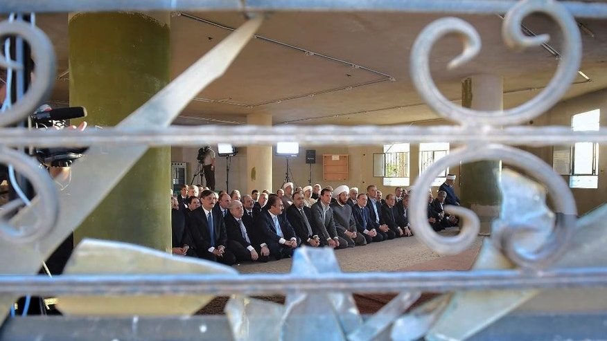 In this photo released on the official Facebook page of the Syrian Presidency, Syrian President Bashar Assad, fifth left, prays at the dawn Eid al-Adha prayers at the Saad ibn Muaaz Mosque in Daraya, a blockaded Damascus suburb, Syria, Monday, Sept. 12, 2016. (Syrian Presidency via Facebook)
