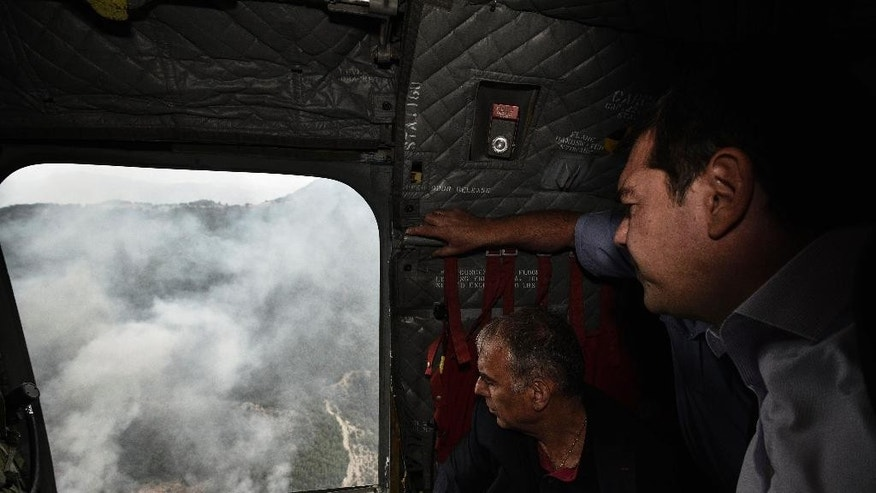In this photo released by Greek Prime Minister's office shows Alexis Tsipras, right, watches from a military helicopter a wildfire on the northern Greek island of Thassos on Monday, Sept. 12, 2016. Greek Prime Minister visits the holiday island in northern Greece where a state of emergency has been declared as a forest fire burns out of control for a third day, gutting homes and small farms. (Andrea Bonetti/Greek Prime Minister's Office via AP)