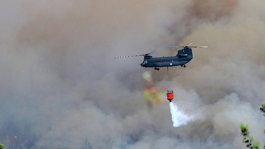 In this Sunday, Sept. 11, 2016 photo a military helicopter drops water over a wildlife in the village of Rahoni on the northern Greek island of Thassos. Prime Minister Alexis Tsipras visits the holiday island in northern Greece on Monday, Sept. 12, 2016 where a state of emergency has been declared as a forest fire burns out of control for a third day, gutting homes and small farms. (Eurokinissi via AP)