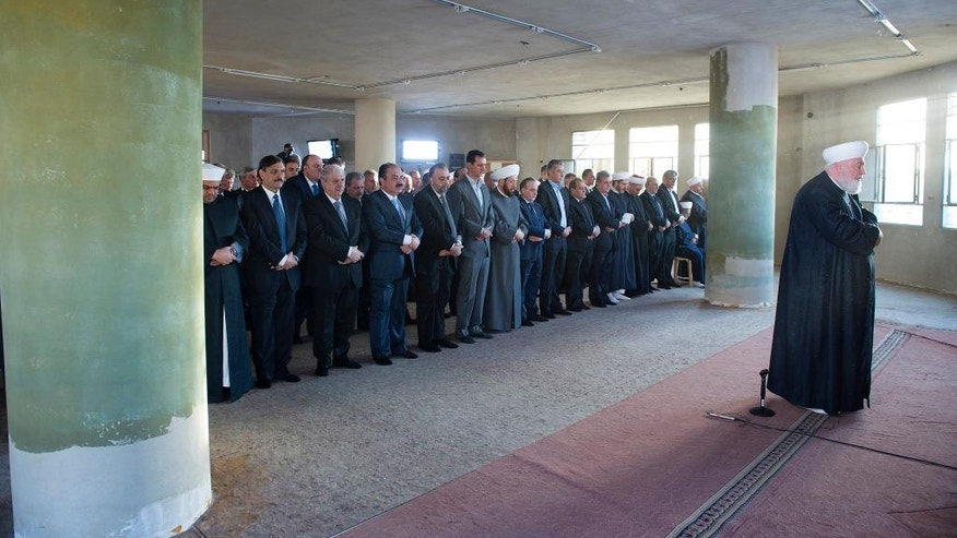 In this photo released on the official Facebook page of the Syrian Presidency, Syrian President Bashar Assad, sixth left, prays the dawn Eid al-Adha prayers at the Saad ibn Muaaz Mosque in Daraya, a blockaded Damascus suburb, Syria, Monday, Sept. 12, 2016. (Syrian Presidency via Facebook)