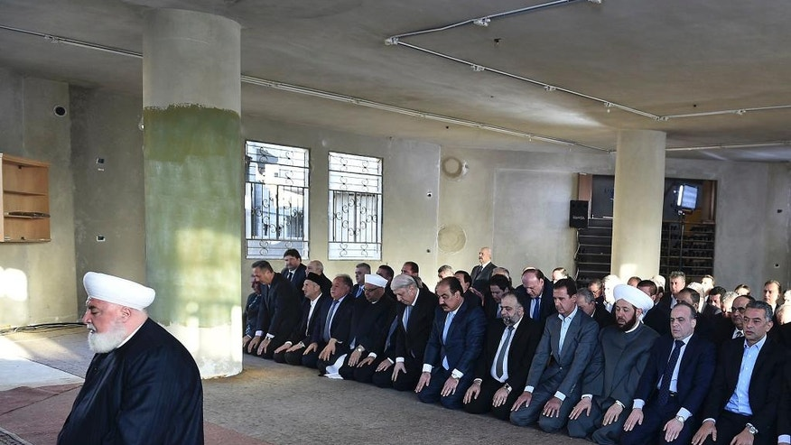 In this photo released on the official Facebook page of the Syrian Presidency, Syrian President Bashar Assad, fourth right, prays at the dawn Eid al-Adha prayers at the Saad ibn Muaaz Mosque in Daraya, a blockaded Damascus suburb, Syria, Monday, Sept. 12, 2016. (Syrian Presidency via Facebook)