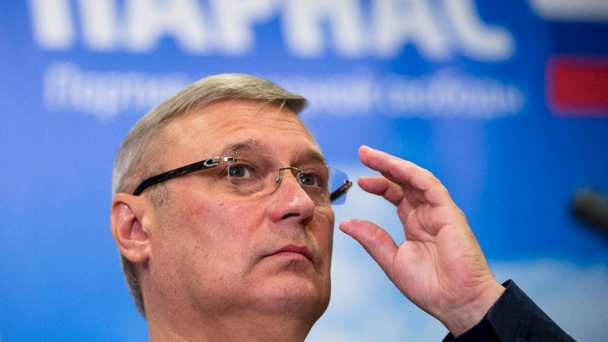 In this Thursday, Aug. 18, 2016 file photo, Russian opposition figure, former Russian Prime Minister Mikhail Kasyanov, chairman of the opposition People's Freedom Party, or Parnas, speaks at a news conference on September's parliamentary elections in Moscow, Russia. Parnas leader Kasyanov expects Maltsev to steal votes from populist parties who criticize the government but stop short of targeting Putin. Poster in the background reads 'Parnas' (AP Photo/Ivan Sekretarev, file)