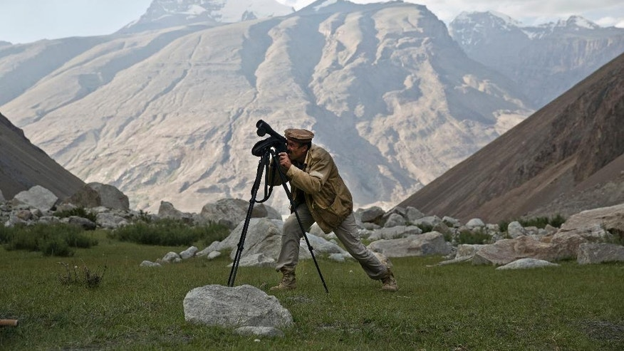 In this Aug. 17, 2016 photo, an employee of the New York-based Wildlife Conservation Society looks for snow leopard in the Wakhan district of Badakhshan province, far northeastern Afghanistan. In this picturesque corner of Afghanistan, a unique conservation effort has helped bring the elusive snow leopard back from the brink and given hope to one of the poorest and most isolated communities on earth. Their numbers declined in recent decades as hunters sought their spotted pelts and farmers killed them to protect livestock. (AP Photos/Massoud Hossaini)