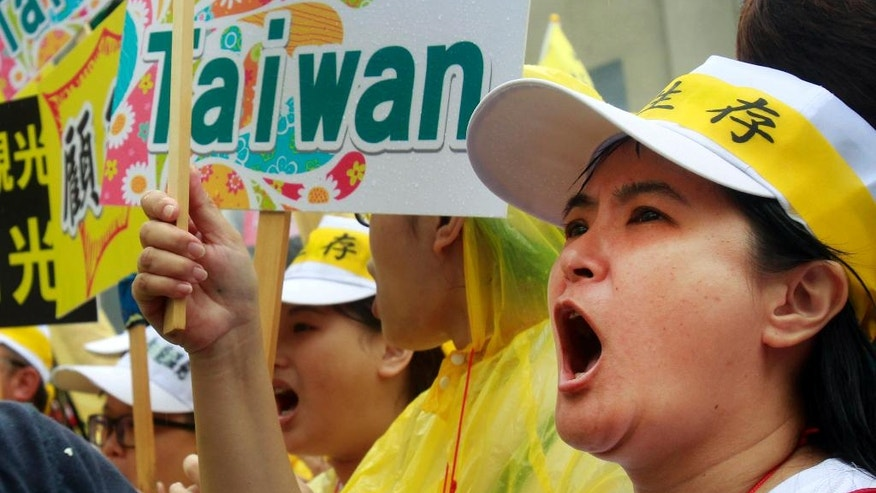 "A tourism industry worker shoots in front a slogan reading ""Welcome to Taiwan"" during a march in Taipei, Taiwan, Monday, Sept. 13, 2016. Thousands of tourism industry workers held a march to call for the government''s attention on the decline of mainland Chinese visitors since President Tsai Ing-wen took office in May. It''s believed that Beijing might have taken the action to tighten its control over Taiwan-bound tourist arrivals after Tsai refused to endorse the concept of a single Chinese nation. (AP Photo/Chiang Ying-ying)"