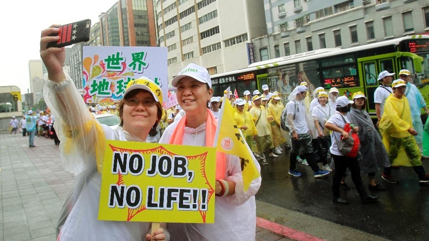 "Two tourism industry workers shoot with a slogan reading ""No Job. No Life!"" during a march in Taipei, Taiwan, Monday, Sept. 13, 2016. Thousands of tourism-related business workers held a march to call for the government''s attention on the decline of mainland Chinese visitors since President Tsai Ing-wen took office in May. It''s believed that Beijing might have taken the action to tighten its control over Taiwan-bound tourist arrivals after Tsai refused to endorse the concept of a single Chinese nation. (AP Photo/Chiang Ying-ying)"