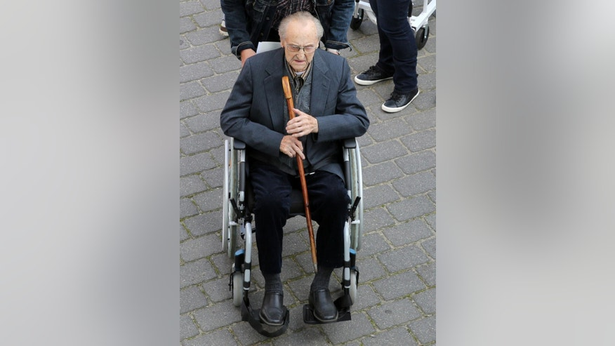 Hubert Zafke  arrives in a wheelchair ahead of his trial in Neubrandenburg, eastern Germany, Monday, Sept. 12, 2016. The  former SS medic who served at the Auschwitz death camp has gone on trial in the northern German city of Neubrandenburg, though questions remain about whether the 95-year-old is fit enough for the proceedings to continue. The trial of Hubert Zafke, scheduled to start in February, had already been postponed three times after Presiding Judge Klaus Kabisch said his health was not good enough to proceed, based upon a doctor's assessment.  (Bernd Wuestneck/dpa via AP)