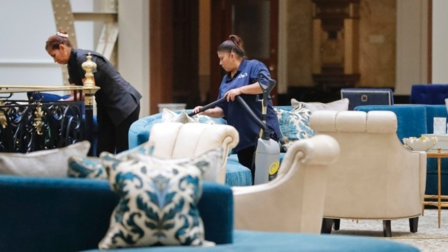 "Workers vacuum furniture in the lobby at the Trump International Hotel in downtown Washington, Monday, Sept. 12, 2016 in Washington. The luxury hotel Donald Trump has built in an iconic downtown Washington building is set to open. The Trump International Hotel will begin serving guests Monday. There won't be any fanfare around the opening, which is known as a ""soft opening."" Grand-opening ceremonies are being planned for October. The Trump Organization won a 60-year lease from the federal government to transform the Old Post Office building on Pennsylvania Avenue into a hotel. (AP Photo/Pablo Martinez Monsivais)"