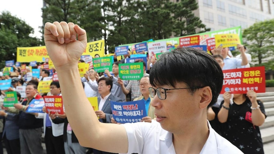 """South Korean shout slogans during a rally denouncing North Korea's latest nuclear test in Seoul, South Korea, Monday, Sept. 12, 2016. North Korea is capable of detonating another nuclear device anytime at one of its unused tunnels at the country's main atomic test site, Seoul official said Monday, three days after the country carried out its fifth bomb explosion. The letters read """"Overthrow Kim Jong Un."""" (AP Photo/Lee Jin-man)"""