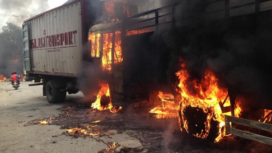 Two trucks that came from the neighboring Tamil Nadu state go up in flames during violence in Bangalore, Karnataka state, India, Monday, Sept. 12, 2016. India's top court on Monday ordered the southern state of Karnataka to release water from a disputed river to neighboring Tamil Nadu after violence erupted in both states over water sharing. (AP Photo/Aijaz Rahi)
