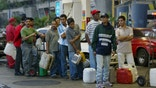 CARACAS, VENEZUELA - DECEMBER 19:  Venezuelans wait in long lines to purchase limited supplies of available gas December 19, 2002 in Caracas, Venezuela. The country is in the 18th day of a nationwide strike which has crippled Venezuela's vital oil industry.  (Photo by Paula Bronstein/Getty Images)