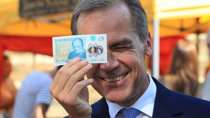 Bank of England Governor Mark Carney holds a new plastic £5 note as he visits Whitecross Street market in London, Tuesday, Sept. 13, 2016. The polymer note is said by the Bank of England to be cleaner, safer and stronger than paper notes, lasting around five years longer. (Jonathan Brady/PA via AP)
