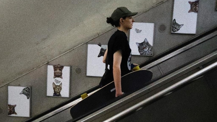 A woman travels on the escalator passing portraits featuring cats, on display, at the Clapham Common Tube station in London, Tuesday, Sept. 13, 2016. Cat lovers in need of a pick-me-up may start gravitating toward London's Clapham Common Tube station. All of the station's customary advertisements have been taken down, replaced by 68 oversized portraits of rather adorable cats.  (AP Photo/Frank Augstein)