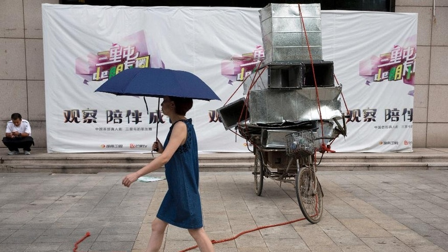 In this Aug. 22, 2016 photo, a woman walks with an umbrella past scavenged air ducts made from aluminum sheet metal in Beijing, China. China's leaders are promising to rein in aluminum production that is flooding global markets and threatening jobs in the United States and Europe, but its producers have ambitious plans to expand. (AP Photo/Ng Han Guan)