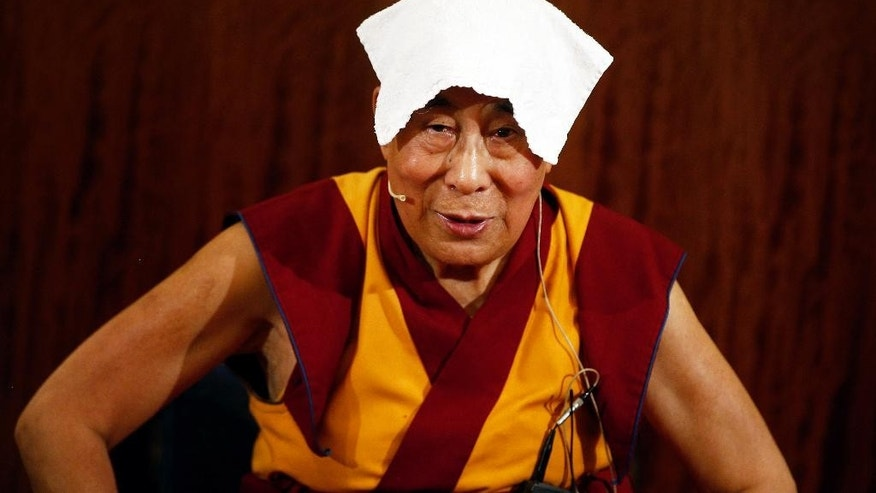 Tibetan spiritual leader, the Dalai Lama wears a towel on his head to cool off, during a press conference , in Paris, Tuesday, Sept. 13, 2016. The Dalai Lama says there should be dialogue with Islamic State extremists to end bloodshed in Syria and Iraq, and argues that religion is never a justification for bloodshed. The spiritual leader is on a six day visit to France. (AP Photo/Thibault Camus)
