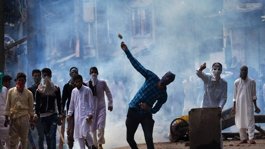 A Kashmiri throws a rock at Indian security personnel during a protest after Eid al-Adha prayers in Srinagar, Indian controlled Kashmir, Tuesday, Sept. 13, 2016. Security forces fired tear gas and shotgun pellets to quell protesters in several places, as a security lockdown marred Eid festivities in the troubled region. Shops and businesses were closed, with a curfew in effect in the entire Kashmir Valley. (AP Photo/Dar Yasin)