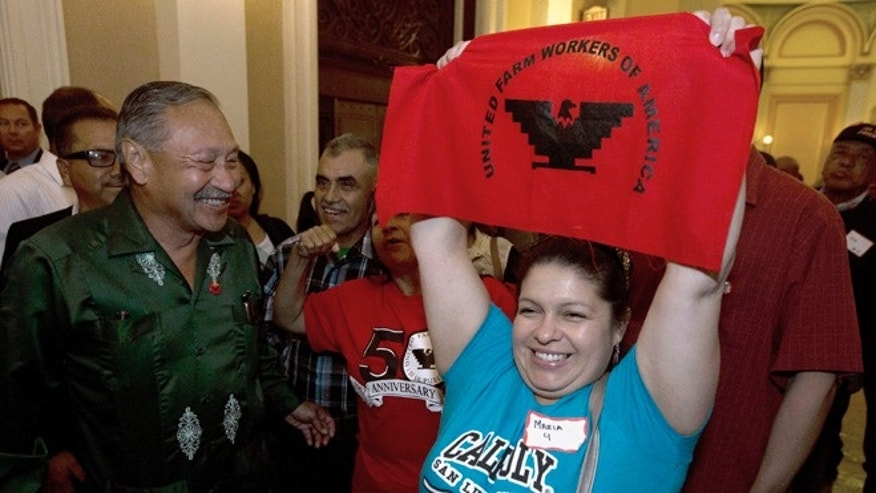 Maria Ceja and other farm workers celebrate outside the Assembly Chambers in Sacramento, Calif. Calif.