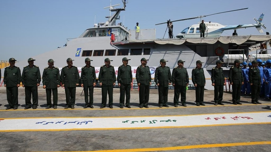Members of Iran's Revolutionary Guard stand in front of a newly inaugurated high-speed catamaran, in the port city of Bushehr, northern  Persian Gulf, Iran, Tuesday, Sept. 13, 2016. Iran's powerful Revolutionary Guard on Tuesday unveiled a new high-speed vessel the force says is capable of carrying a helicopter and up to 100 people, Iranian state TV reported. The report follows a series of close encounters between American warships and Guard vessels in the Persian Gulf. (AP Photo/Hossein Ostovar/Tasnim News Agency)
