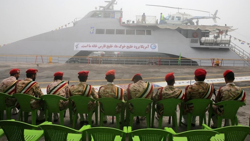 Members of Iran's Revolutionary Guard sit in front of a newly inaugurated high-speed catamaran, in the port city of Bushehr, northern  Persian Gulf, Iran, Tuesday, Sept. 13, 2016. Iran's powerful Revolutionary Guard on Tuesday unveiled a new high-speed vessel the force says is capable of carrying a helicopter and up to 100 people, Iranian state TV reported. The report follows a series of close encounters between American warships and Guard vessels in the Persian Gulf. (AP Photo/Hossein Ostovar/Tasnim News Agency)