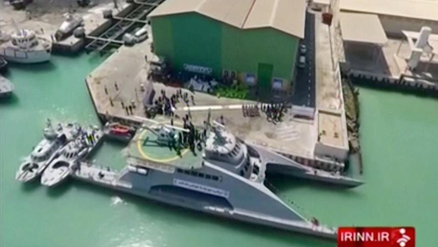 In this frame grab from video provided by IRINN, Iranian TV, a new catamaran vessel is unveiled in the port of Bushehr, Iran, Tuesday, Sept. 13, 2016. Iran's state TV said the country's Revolutionary Guard unveiled a new high-speed vessel capable of carrying a helicopter and up to 100 people. The report follows an increase in the frequency of close encounters between American warships and Guard vessels in the Persian Gulf. (IRINN-Iranian TV via AP)