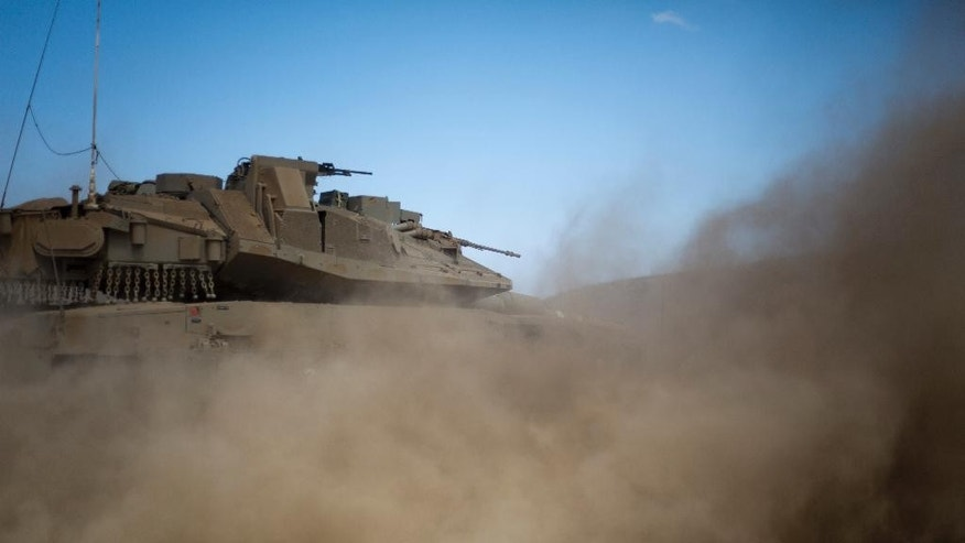 An Israeli tank drives  during training in the Israeli-controlled Golan Heights, near the border with Syria, Tuesday, Sept. 13, 2016. Israel is denying Syrian government claims that its forces shot down a warplane and a drone near the Israeli-controlled part of the Golan Heights. Israeli warplanes have conducted several air raids on Syrian army positions over the past weeks after stray shells hit the Israeli-occupied area. (AP Photo/Ariel Schalit)
