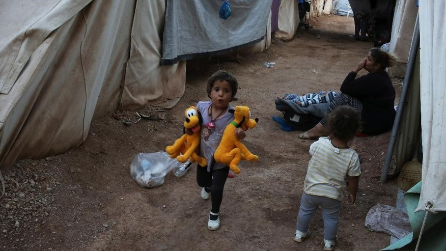 A little girl runs among tents at Ritsona refugee camp which hosts about 600 refugees and migrants, north of Athens, Monday, Sept. 12, 2016. The European Union will add 115 million euros ($129 million) in funding to humanitarian organizations in Greece to assist programs for refugees and migrants before the winter, officials said Saturday. (AP Photo/Petros Giannakouris)
