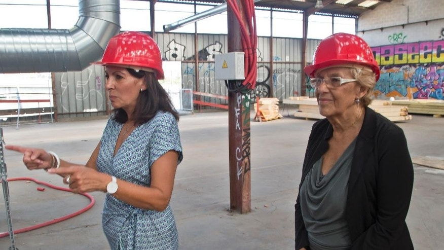 Mayor of Paris Anne Hidalgo, left, points the direction to Mayor of Madrid Manuela Carmena as they visit a construction site of a reception center for migrants in Paris, Monday, Sept. 12, 2016. A new reception center for migrants in the French capital, is scheduled to open next month, in an unusual and controversial effort to cope with Europe's migrant crisis. (AP Photo/Michel Euler)
