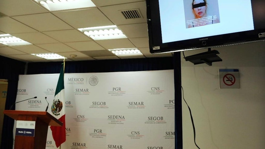 A woman identified by authorities as Clara Laborin Archuleta, wife of jailed drug lord Hector Beltran Leyva, is shown on a monitor during a news conference by federal police in Mexico City, Tuesday, Sept. 13, 2016. Federal police say Archuleta was arrested on Monday in the northern state of Sonora. She's alleged to have been involved in efforts to reassert her husband's gang's control over criminal operations in the Pacific coast resort city of Acapulco. (AP Photo/Marco Ugarte)