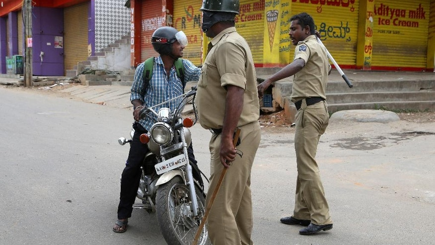 An Indian policeman hits a motorcyclist for defying curfew, a day after angry mobs burnt and vandalized buses from the neighboring Tamil Nadu state, in Bangalore, capital of the southern Indian state of Karnataka, Tuesday, Sept. 13, 2016. Incidents of looting and vandalism eased Tuesday in parts of India's information technology hub of Bangalore after authorities imposed a curfew amid widespread protests overnight over India's top court ordering the southern state of Karnataka to release water from a disputed river to the neighboring state. (AP Photo/Aijaz Rahi)