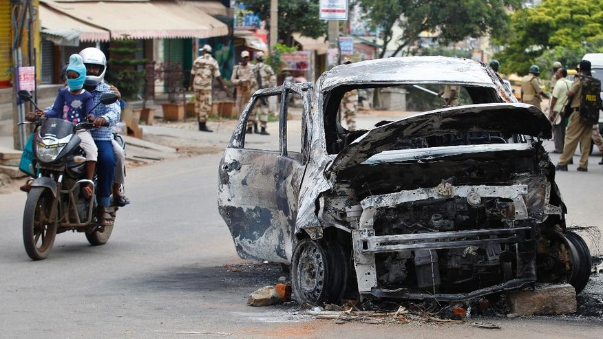 A motorist rides past charred remains of a car, a day after it was burnt by an angry mob, in Bangalore, capital of the southern Indian state of Karnataka, Tuesday, Sept. 13, 2016. Incidents of looting and vandalism eased Tuesday in parts of India's information technology hub of Bangalore after authorities imposed a curfew amid widespread protests overnight over India's top court ordering the southern state of Karnataka to release water from a disputed river to the neighboring state of Tamil Nadu. (AP Photo/Aijaz Rahi)