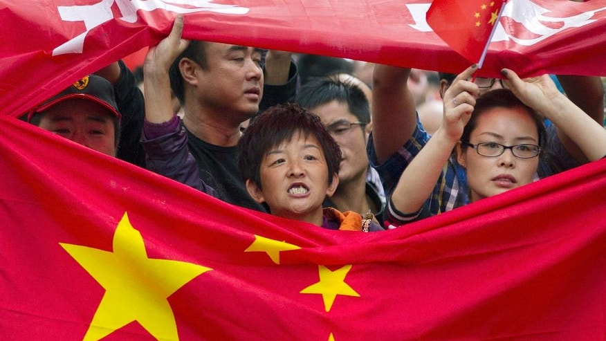 FILE - In this Tuesday, Sept. 18, 2012, file photo, Chinese demonstrators hold national flags while marching on a street during a protest against Japan in Chengdu, southwest China's Sichuan province Tuesday, Sept. 18, 2012. The annual Pew Research Center survey, released Tuesday in Washington, D.C., found that while the views China and Japan have of each other have improved slightly in the past two to three years, they remain overwhelmingly negative and worse than a decade ago. (AP Photo/Andy Wong, File)