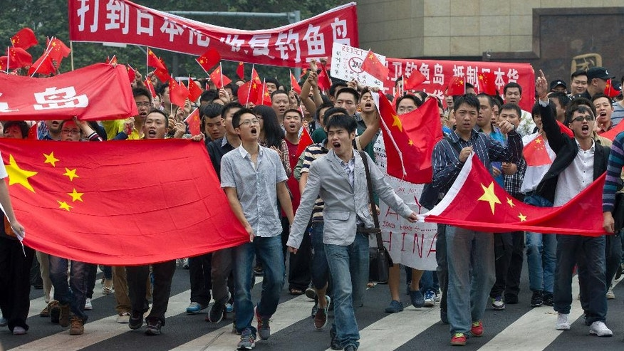"""FILE - In this Tuesday, Sept. 18, 2012, file photo, Chinese demonstrators hold national flags and banners with the words """"Beat down Japan, take back Diaoyu Island"""" while marching on a street during a protest against Japan in Chengdu, southwest China's Sichuan province. The annual Pew Research Center survey, released Tuesday in Washington, D.C., found that while the views China and Japan have of each other have improved slightly in the past two to three years, they remain overwhelmingly negative and worse than a decade ago. (AP Photo/Andy Wong, File)"""