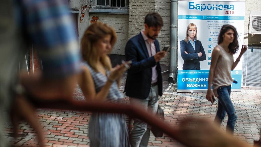In this photo taken Friday, July 29, 2016 people stand by an election poster of opposition activist, Maria Baronova, running for parliamentary election in Moscow, Russia. Baronova's activist nature propelled her into the spotlight as a spokeswoman for the protest organizers. Five years later, the trained chemist is taking her activism in a new direction by running for parliament. (AP Photo/Alexander Zemlianichenko)