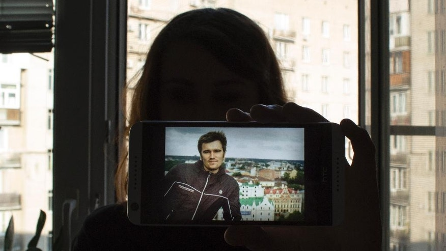 In this photo taken on Monday, Aug. 1, 2016, Anna Gaskarova, journalist and wife of political prisoner Andrei Gaskarov, holds a photo of her husband in Moscow, Russia. In 2013, her husband Alexei Gaskarov was imprisoned for his participation in the Bolotnaya protests, convicted of attacking police at the rally. Since then, Anna has repeatedly appealed for her husband's early release, saying that the allegations are false and politicized. (AP Photo/Francesca Ebel)