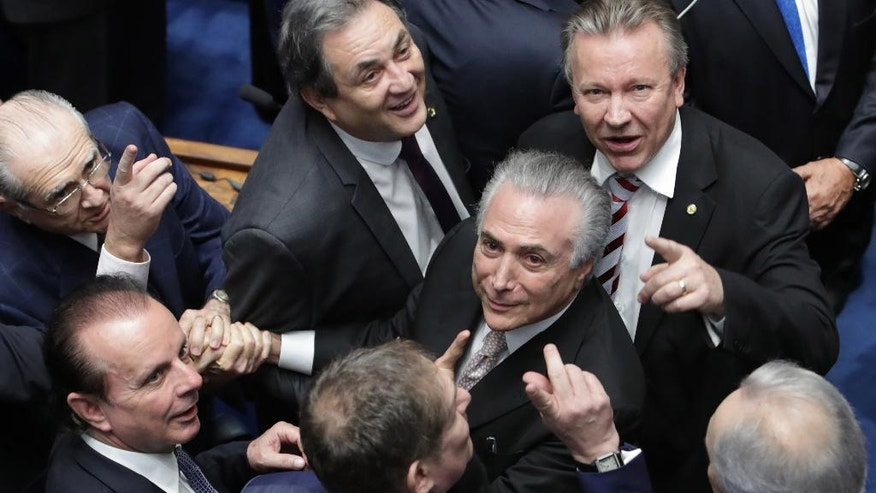 FILE - In this Aug. 31, 2016 file photo, senators greet Brazil's President Michel Temer, center, as he arrives to take the presidential oath at the National Congress, in Brasilia, Brazil. Two weeks after his predecessor's ouster, Temer has rubbed elbows with world leaders in China, been vociferously booed at important national events and signaled he will move forward with unpopular reforms, such as trimming pension benefits.  (AP Photo/Eraldo Peres)