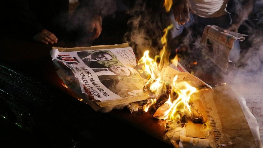 FILE - In this Sept. 4, 2016 file photo, demonstrators burn a poster of Brazil's President Michel Temer, during protests demanding Temer's removal and call for new elections, in Sao Paulo, Brazil. Many Brazilians believe that the impeachment process against Dilma Rousseff Rousseff was a sham. Rousseff and her supporters accuse Temer, who was her vice president, of being one of the ringleaders of her ouster, accusations he denies. (AP Photo/Nelson Antoine, File)