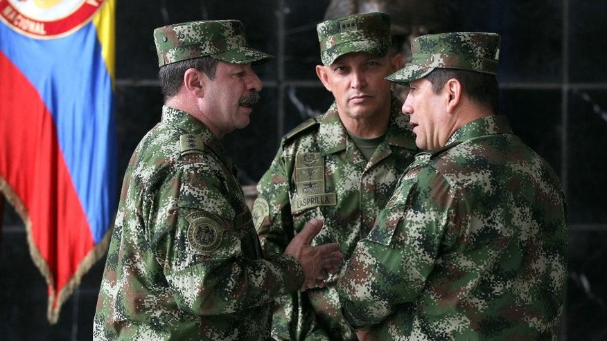 FILE - In this Feb. 18, 2014, file photo, the new Colombian armed forces commander Gen. Juan Pablo Rodriguez, right, talks to newly appointed chief of staff Gen. Javier Florez, left, and army commander Gen. Jaime Lasprilla, center, after a press conference where Defense Minister Juan Carlos Pinzon announced the firing of the former armed forces chief Gen. Leonardo Barrero in Bogota, Colombia. After battling the Revolutionary Armed Forces of Colombia for 40 years,  Gen. Florez's mission is now to ensure that thousands of the guerrillas safely disarm before returning to civilian life under a historic peace deal reached in 2016. (AP Photo/Fernando Vergara, File)