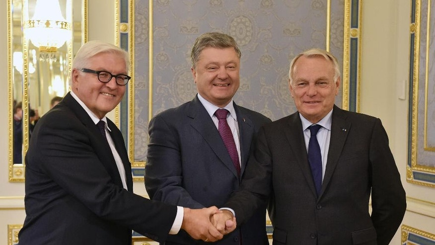 Ukrainian President Petro Poroshenko, centre, shake hands with French Foreign Minister Jean-Marc Ayrault , right, and his German counterpart Frank-Walter Steinmeier during their visit in Kiev, Ukraine, Wednesday, Sept. 14, 2016, for talks with top Ukrainian officials on ways to resolve one of Europe's deadliest wars in more than a decade and prop up a tentative ceasefire. (Genya Savilov/pool photo via AP)