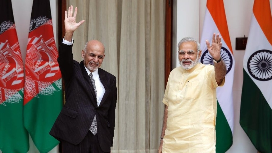 Indian Prime Minister Narendra Modi, right, and Afghan President Ashraf Ghani wave at the media before a meeting in New Delhi, India, Wednesday, Sept. 14, 2016. President Ghani is on a two-day visit to India. (AP Photo/Manish Swarup)
