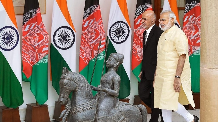 Indian Prime Minister Narendra Modi, right, walks with Afghan President Ashraf Ghani, before a meeting in New Delhi, India, Wednesday, Sept. 14, 2016. President Ghani is on a two-day visit to India. (AP Photo/Manish Swarup)