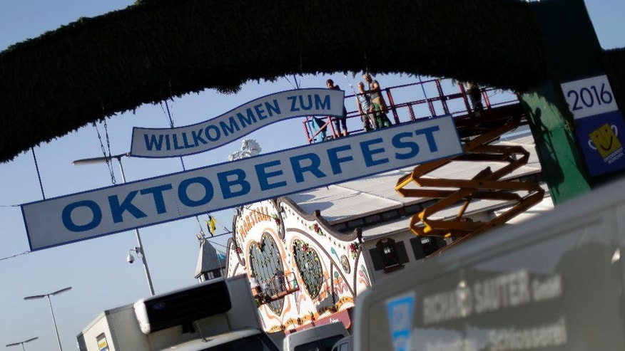 Employees prepare a sign at the main entrance of the 'Theresienwiese', the area of the Oktoberfest, in Munich, Germany, Wednesday, Sept. 14, 2016. Authorities are stepping up security for this year's Oktoberfest, which is expected to draw 6 million visitors in the Bavarian capital. The world's largest beer festival will be held from Sept. 17 to Oct. 3, 2016. (AP Photo/Matthias Schrader)