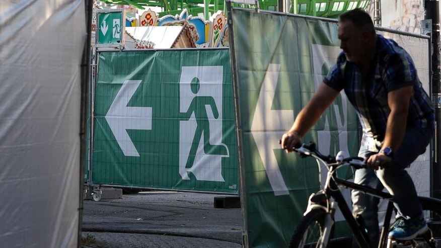 A cyclist stops besides fences at the 'Theresienwiese', the area of the Oktoberfest, in Munich, Germany, Wednesday, Sept. 14, 2016. Authorities are stepping up security for this year's Oktoberfest, which is expected to draw 6 million visitors in the Bavarian capital. The world's largest beer festival will be held from Sept. 17 to Oct. 3, 2016. (AP Photo/Matthias Schrader)