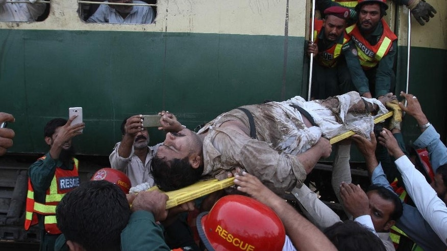 Pakistani volunteers remove an injured passenger from a train that collided with a freight train near Multan, Pakistan, Thursday, Sept. 15, 2016. Scores of passengers were killed and many others were hurt Thursday when a passenger train collided with a freight train near the central Pakistan city of Multan, rescuers and a railway officials said. (AP Photo/Asim Tanveer)